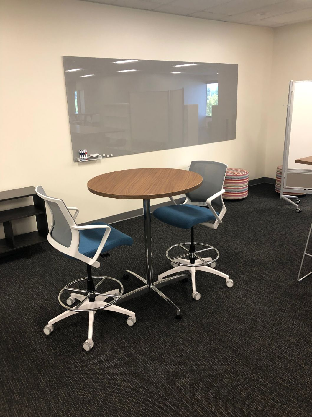 High-top table with white ergonomic office chairs